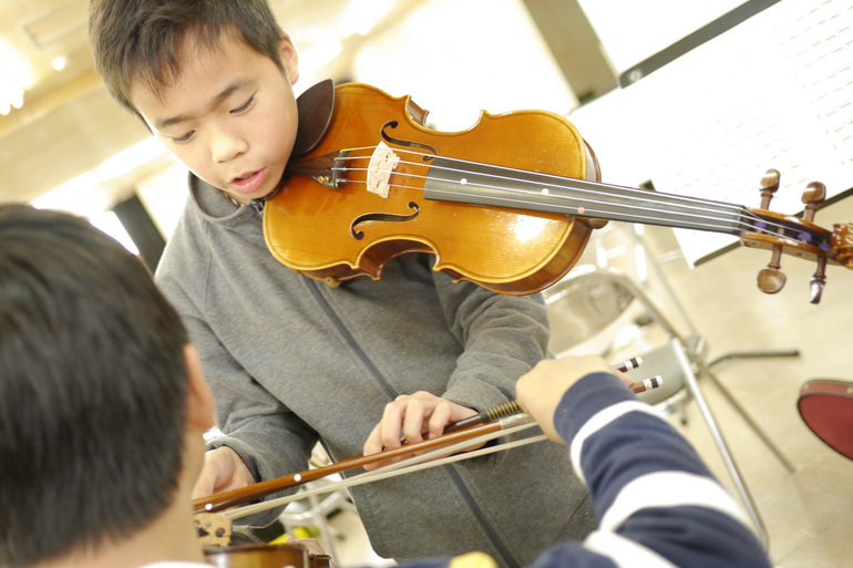 後輩に楽器の持ち方を指導する半谷くん